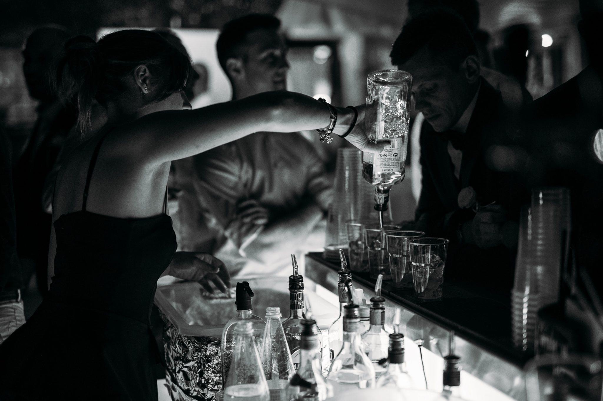 una barista prepara i cocktail agli invitati