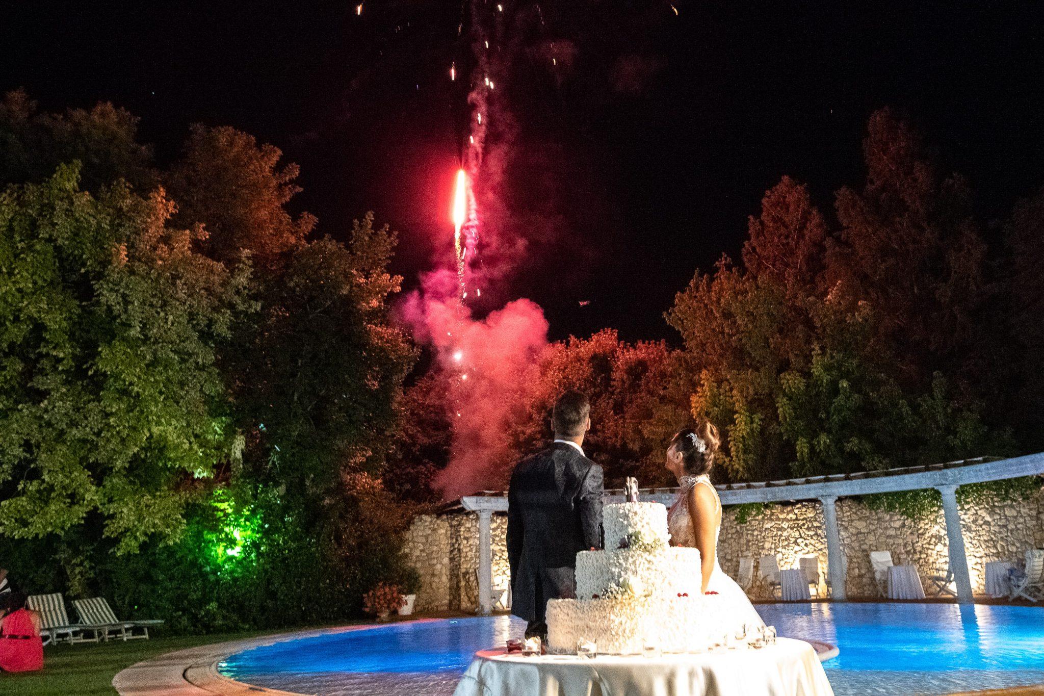 gli sposi con alle spalle la torta nuziale guardano i fuochi d'artificio