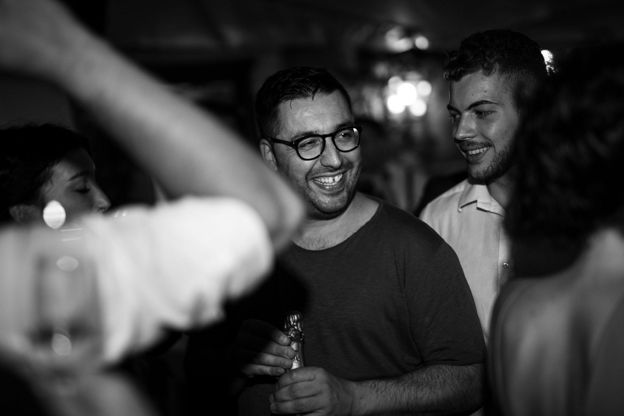 un'invitato degli sposi mentre ride con altri invitati