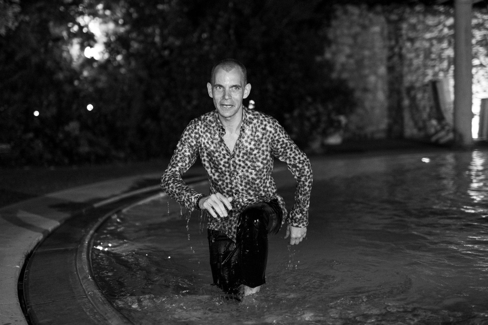 un'invitato fa il bagno in piscina di notte tutto vestito