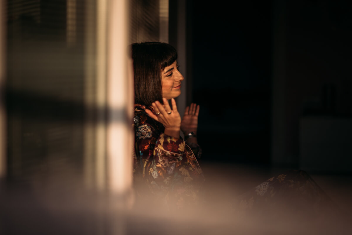 ragazza seduta in camera con la luce del tramonto che passa dalla finestra