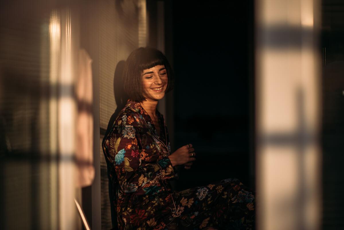 ragazza ride seduta nel pavimento della sua stanza con la luce del tramonto