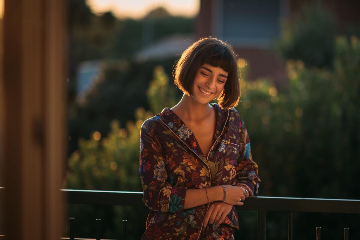 ragazza sorride pensieroso con il tramonto alle spalle