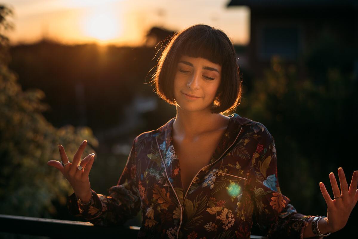 ragazza balla sul terrazzo con il tramonto alle spalle