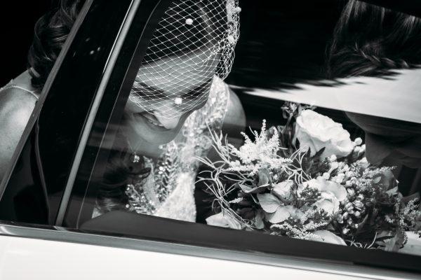la sposa in macchina con il bouquet in mano