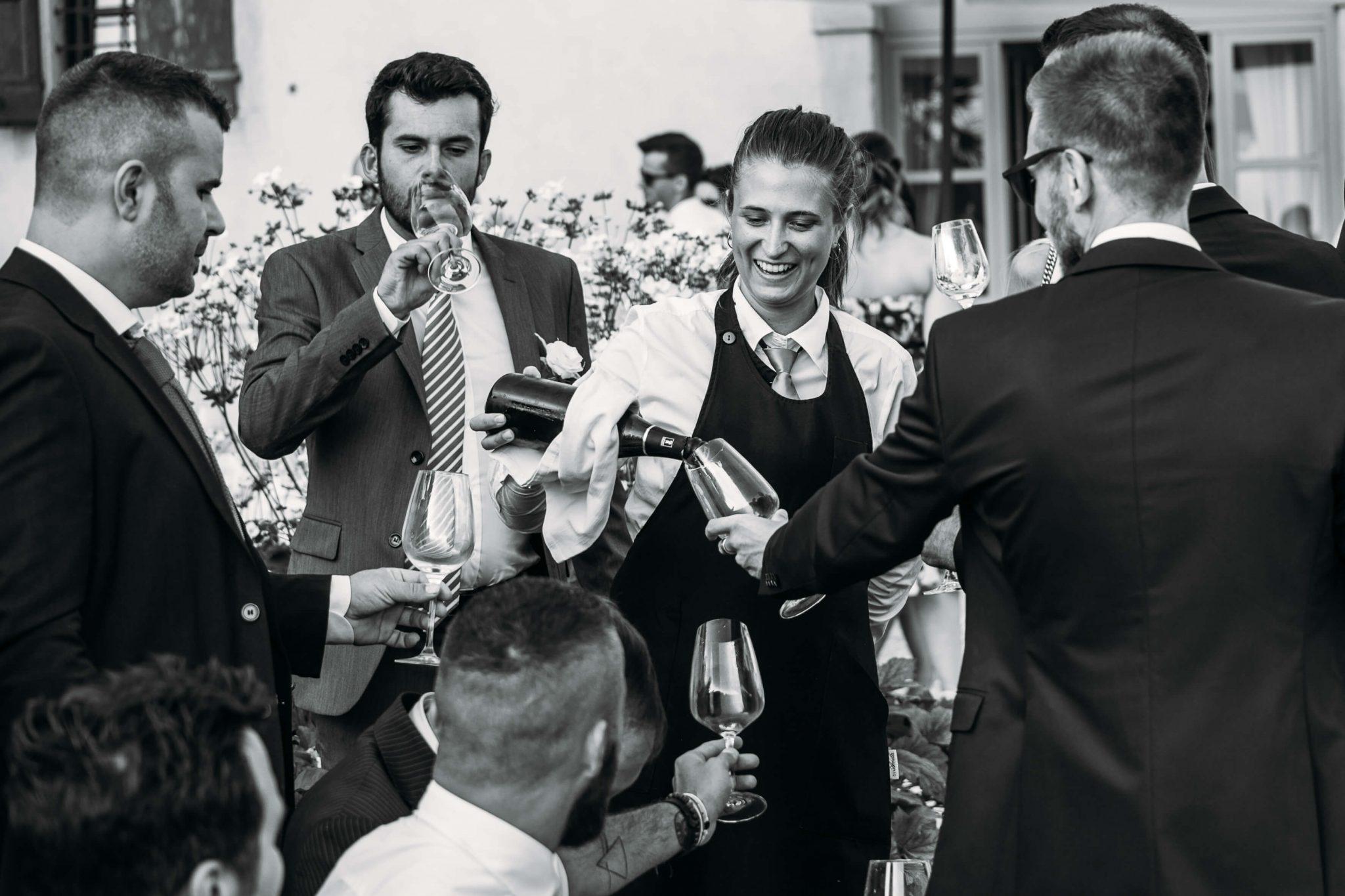 una cameriera serve agli invitati il vino