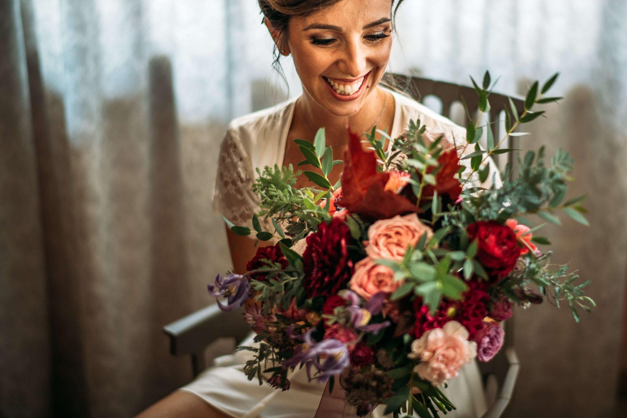 la sposa sorride felice tenendo in mano il bouquet