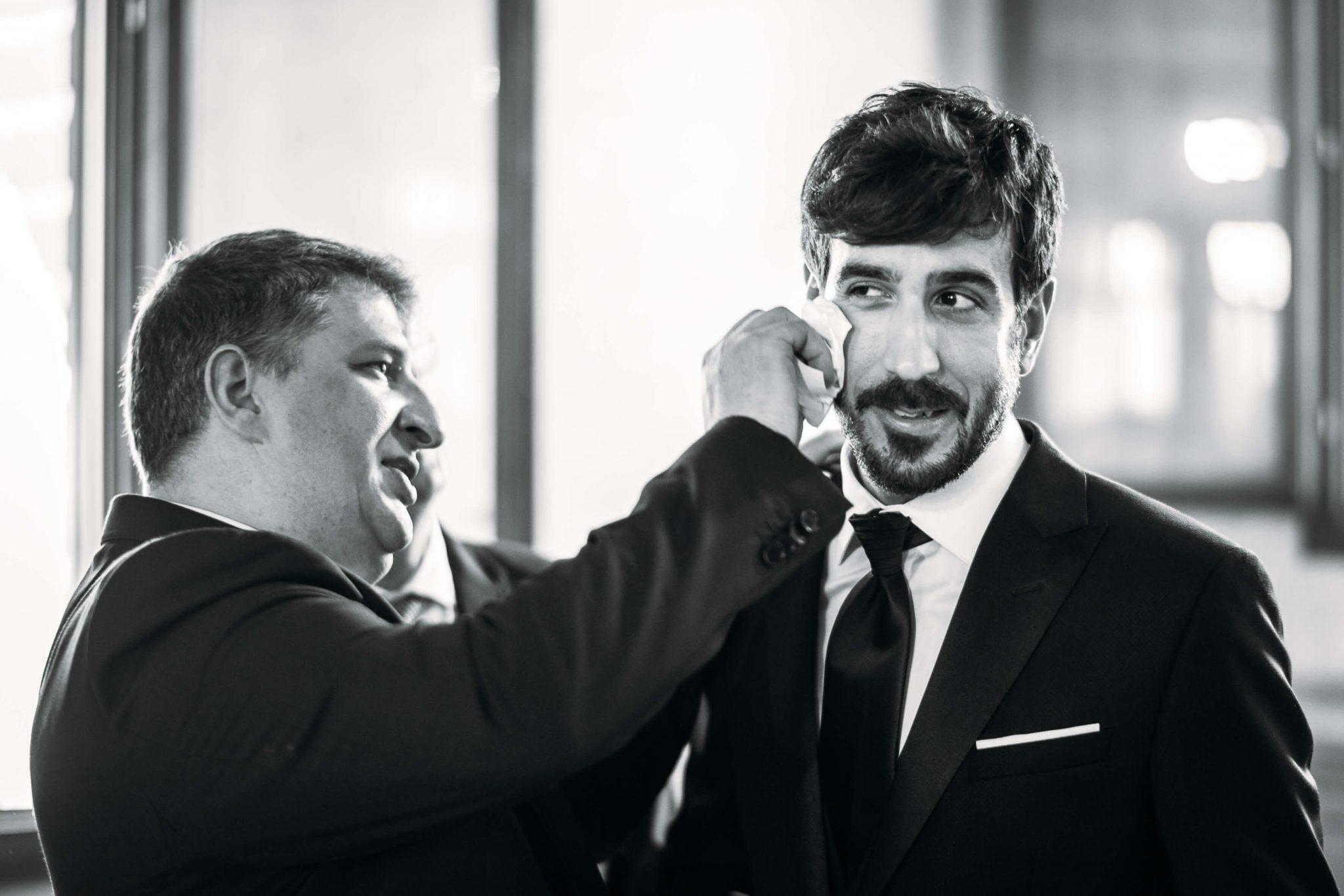 un amico asciuga il sudore dello sposo con un fazzoletto prima della cerimonia