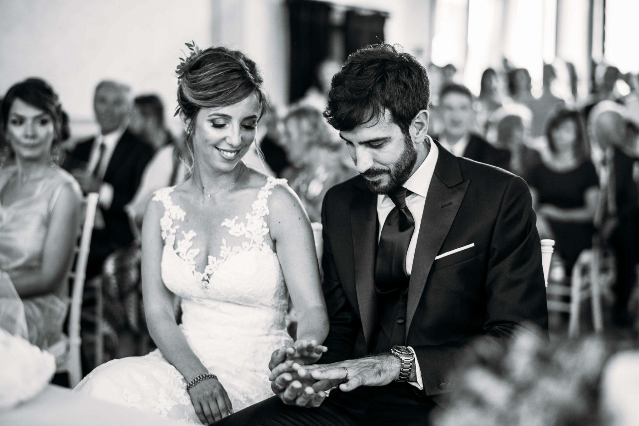 la sposa felice guarda la mano dello sposo con la fede davanti all'altare