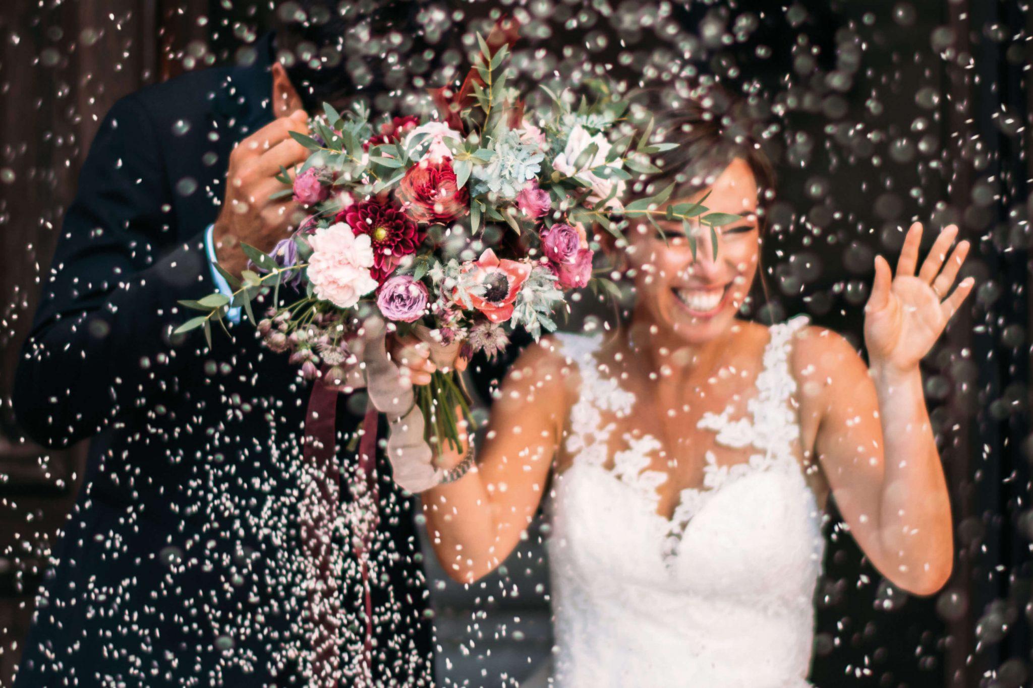 il primo piano del bouquet della sposa durante il lancio del riso fuori dalla chiesa