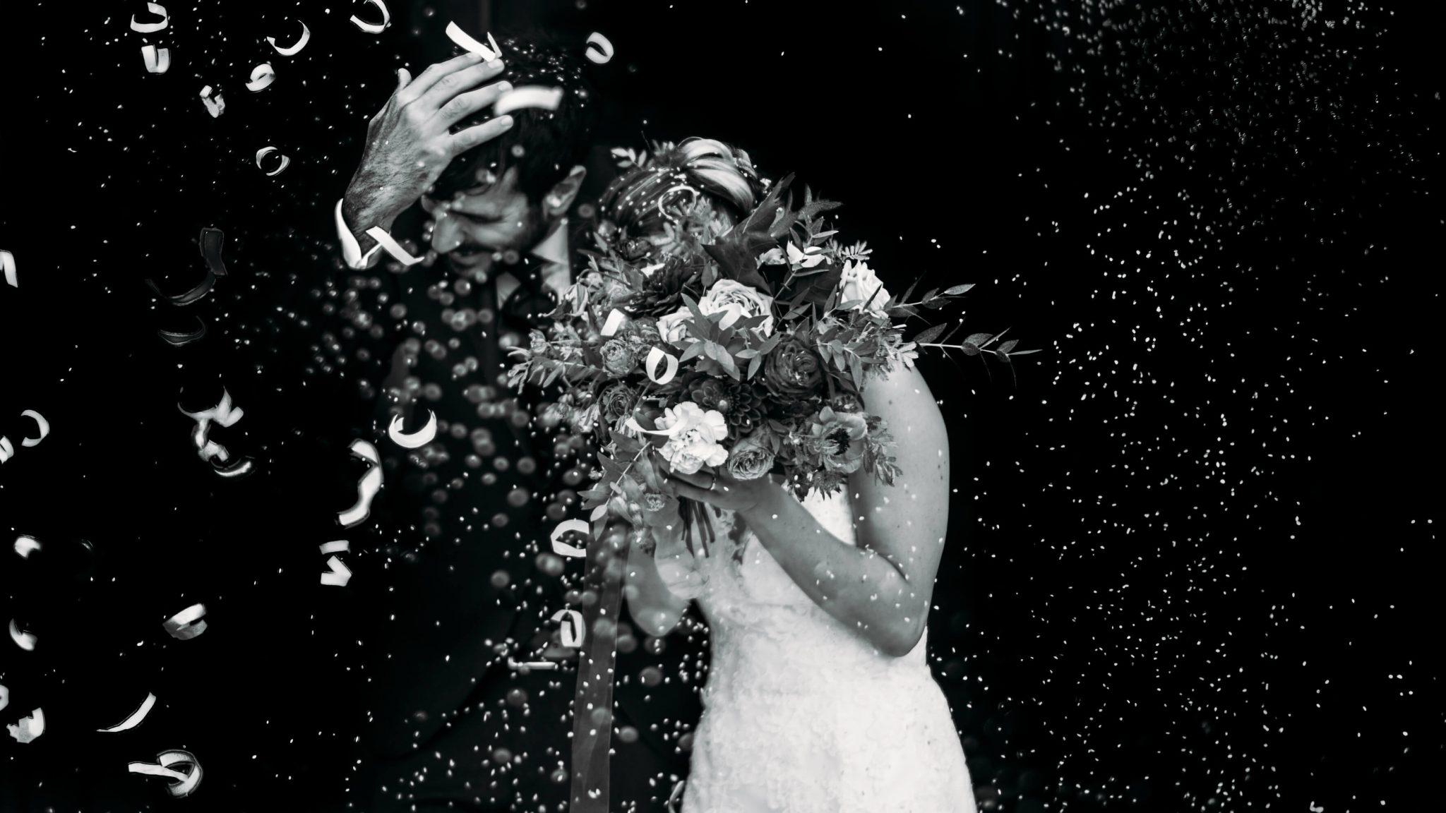 gli sposi all'uscita dalla chiesa si coprono con il bouquet durante il lancio del riso