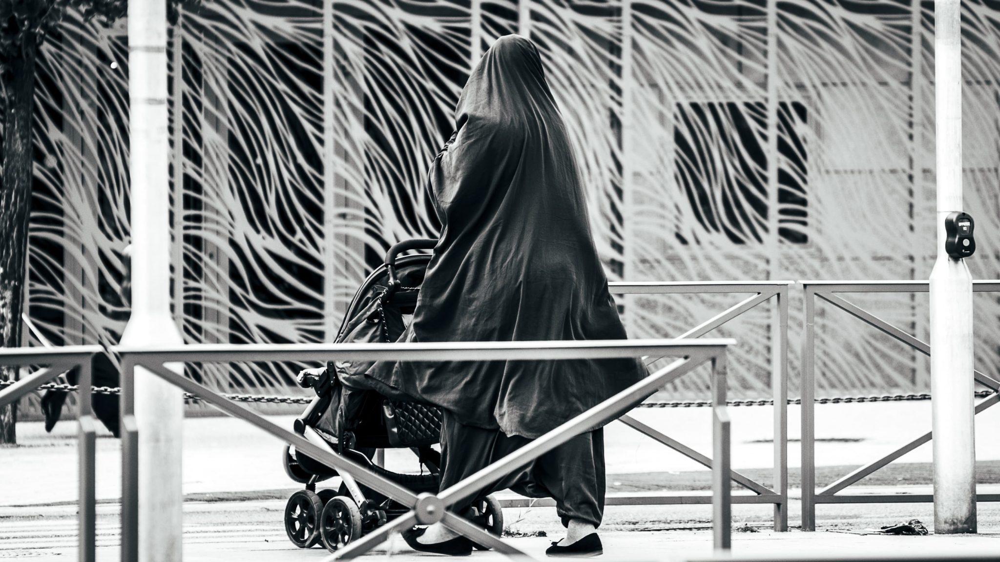 una donna con il velo mentre passeggia per strada con il passeggino