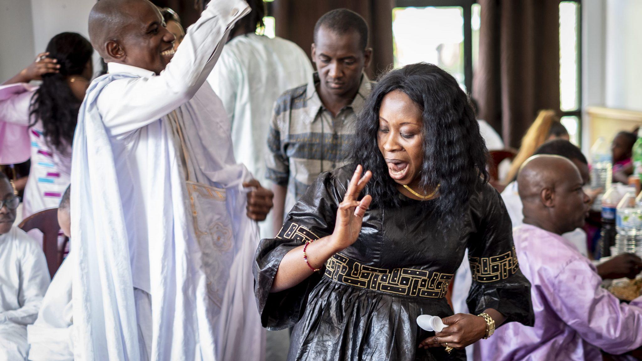 una donna di origine africana balla divertita tra gli invitati della festa