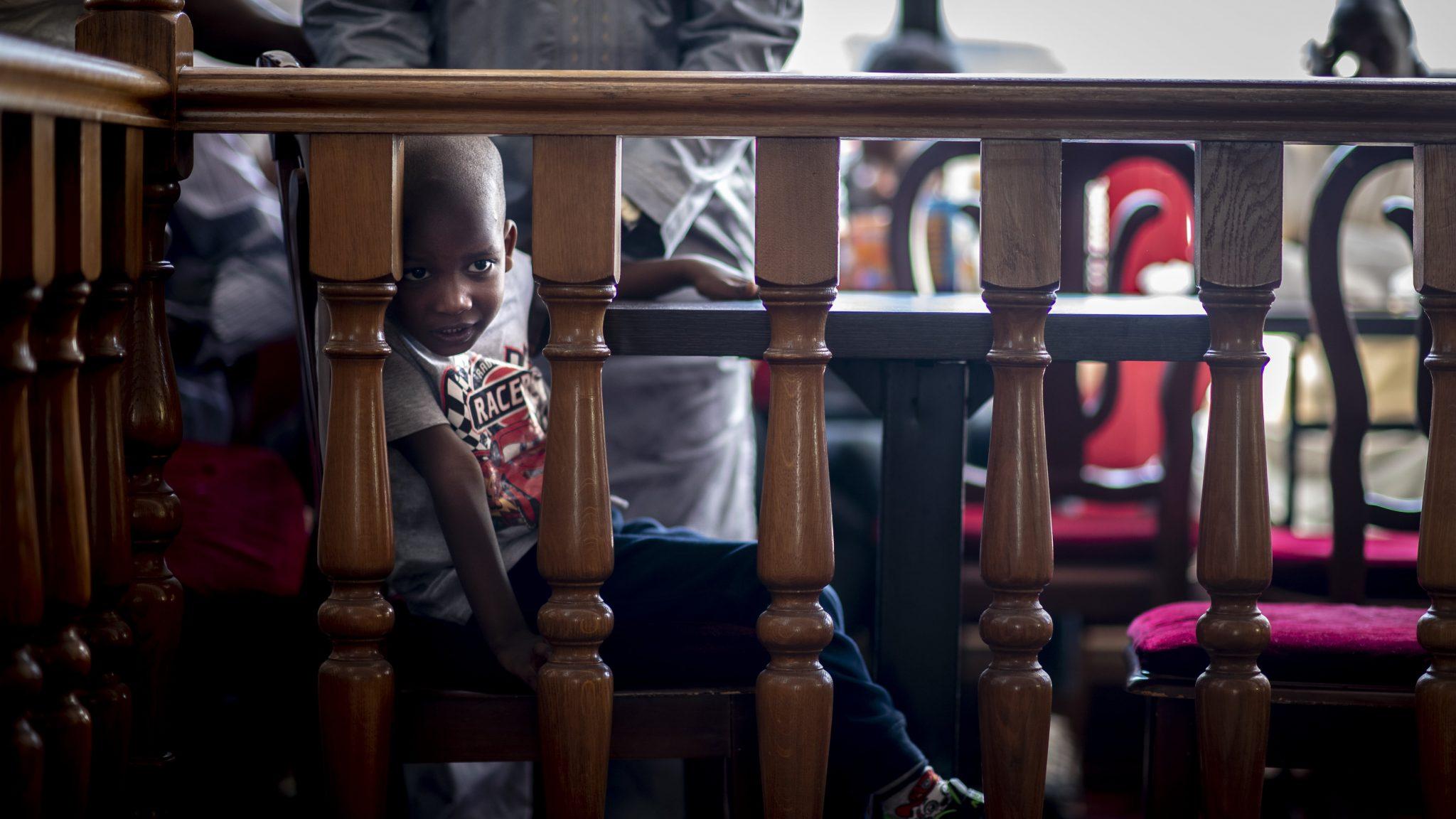 un bambino guarda tra la staccionata del ristorante mentre è seduto al tavolo