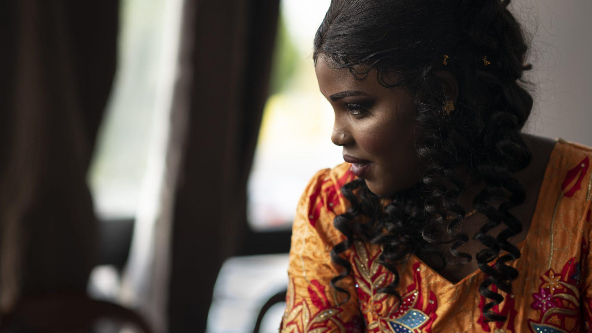 la sposa africana mentre guarda fuori dalla finestra