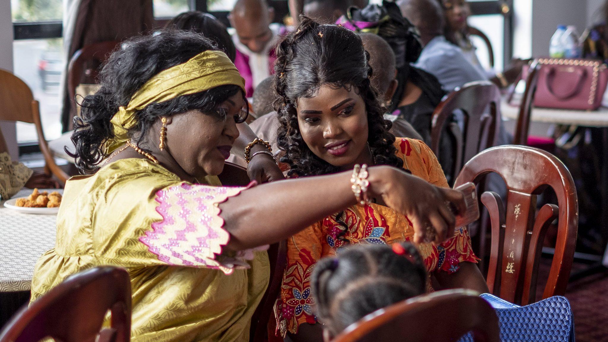 la sposa africana si fa un selfie con un'invitata mentre indossano abiti tradizionali