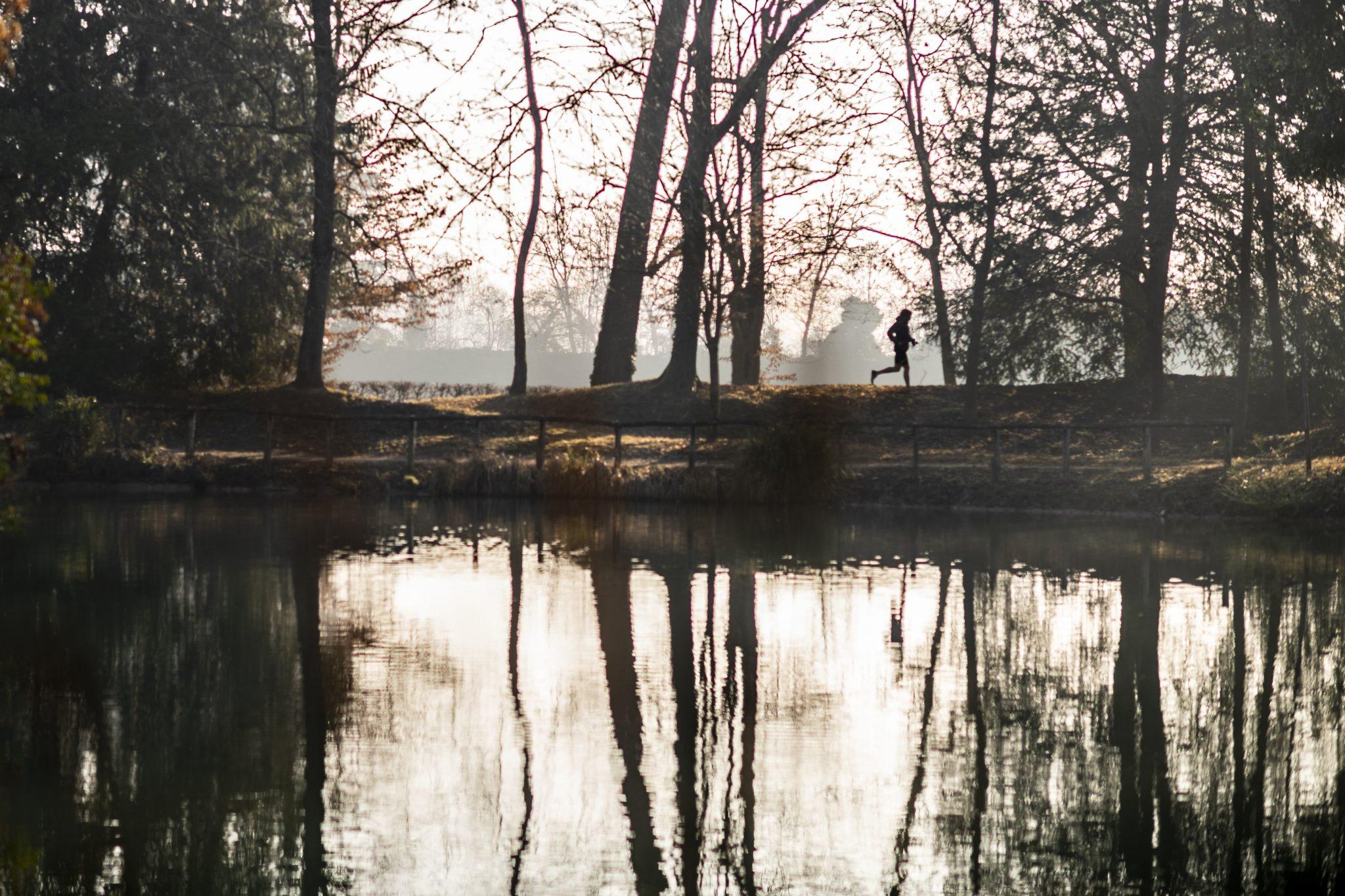 il corridore famoso mentre fa il suo allenamento quotidiano nel parco con il fiume
