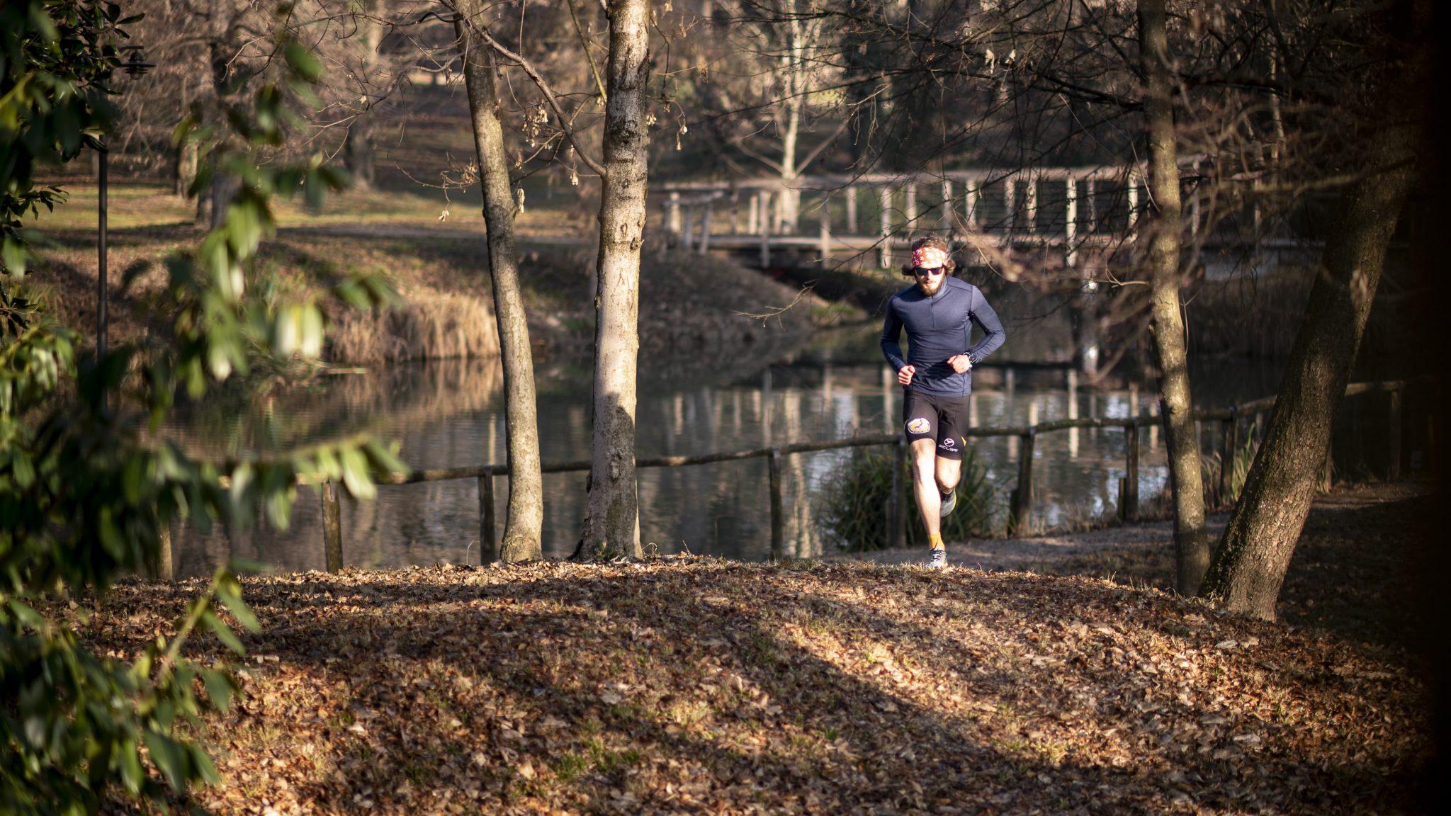 il corridore famoso corre nel parco con il fiume alle sue spalle