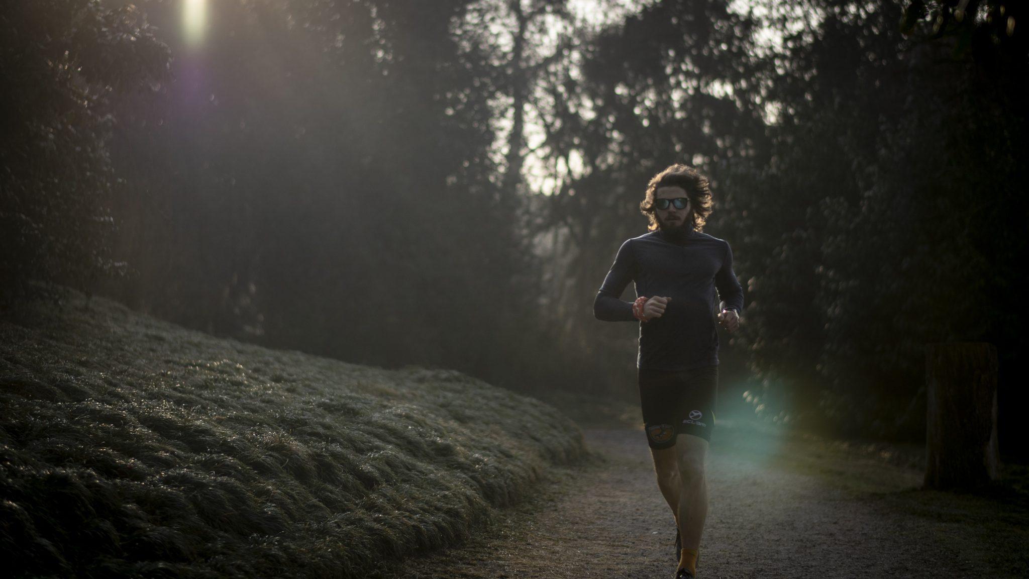 il corridore famoso mentre corre di mattina presto nella foresta
