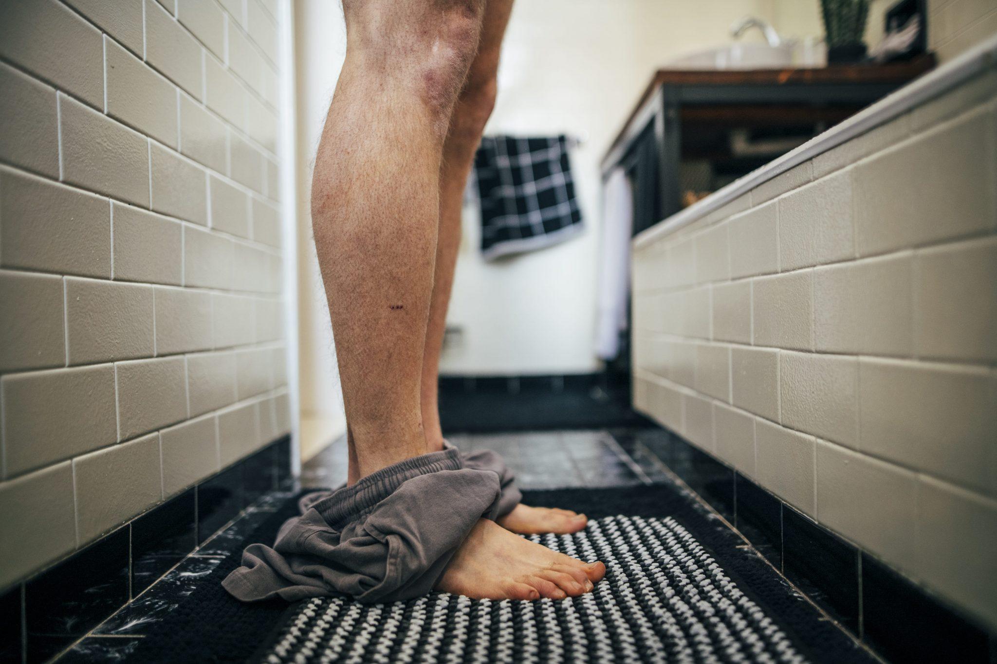 il dettaglio delle gambe con i pantaloncini per terra prima di entrare nella doccia