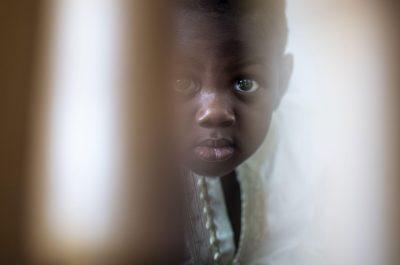 un bambino di origine africana guarda il fotografo da dietro una porta