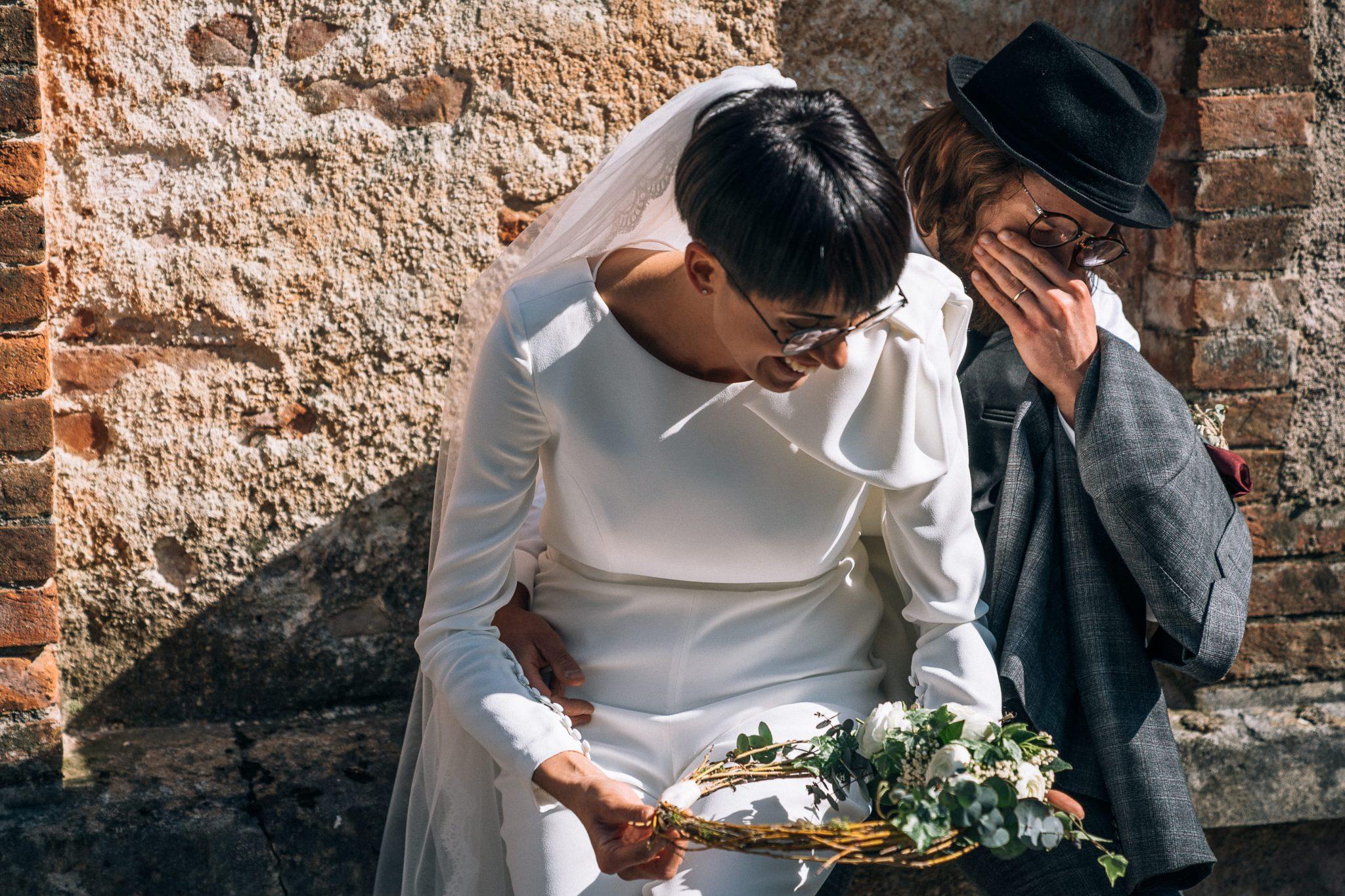 lo sposo si commuove mentre la sposa ride sopra le sue ginocchia