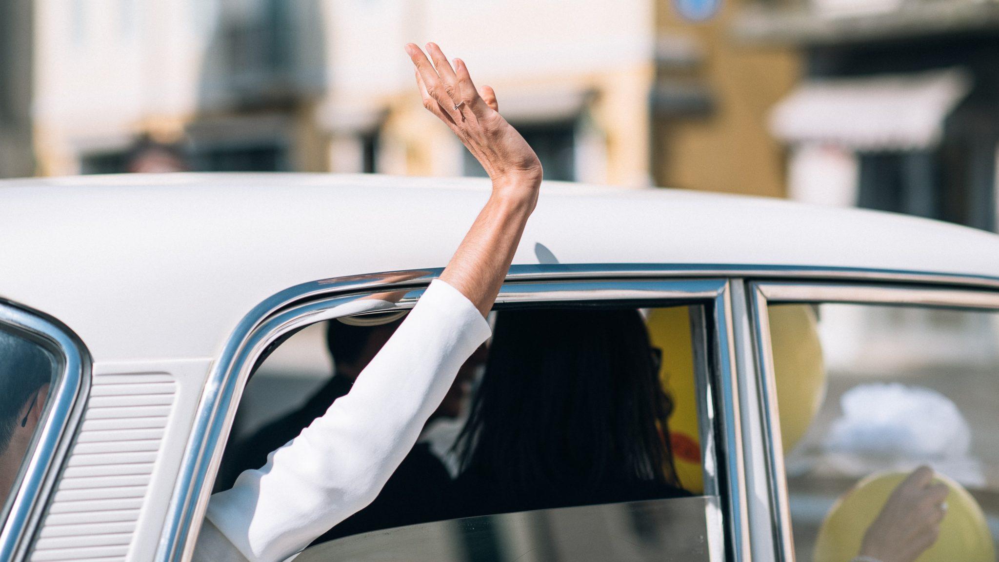 il primo piano della mano della sposa mentre saluta gli invitati fuori dal finestrino della macchina
