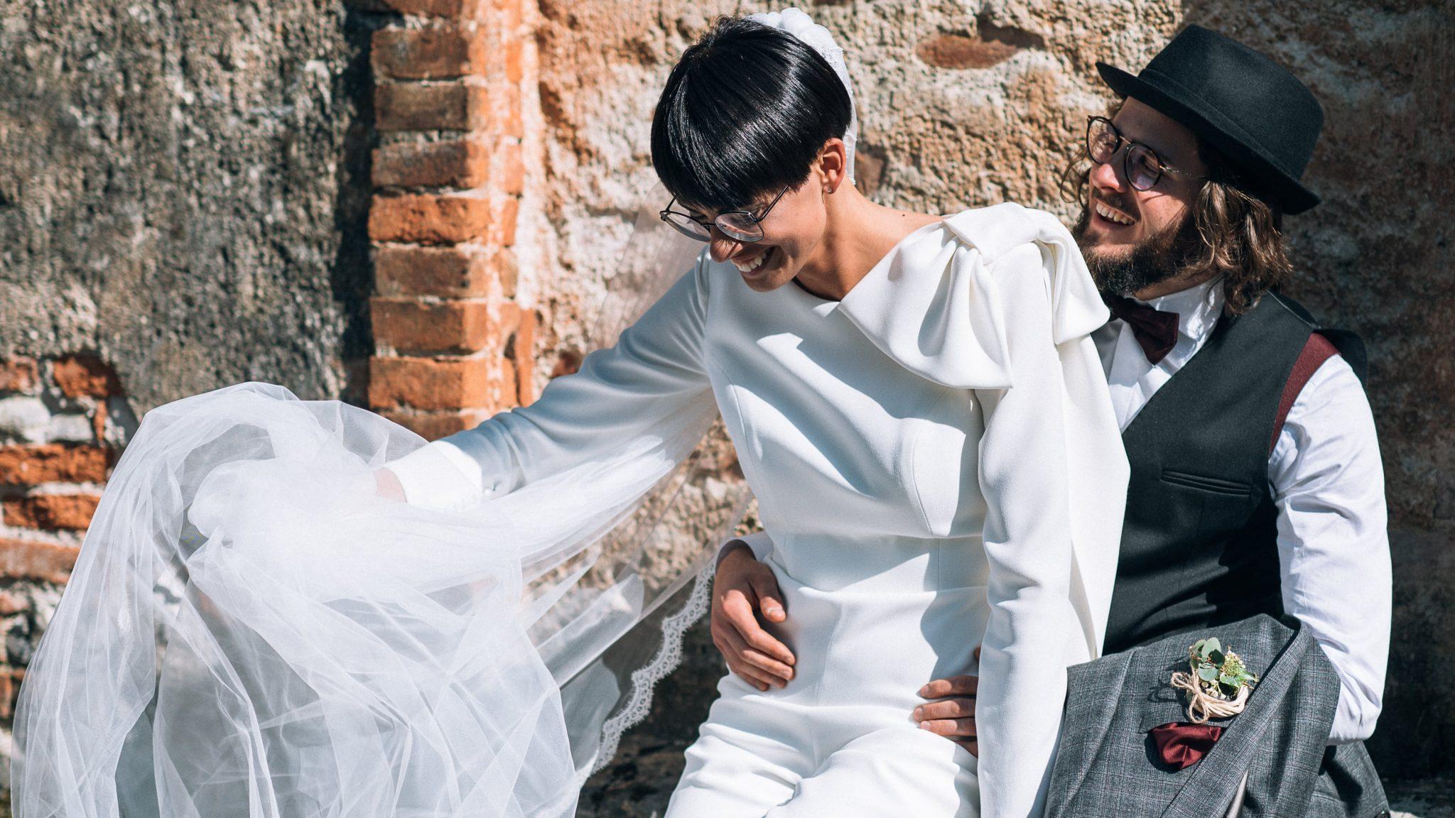 la sposa sorride mentre si sposta il velo sulle ginocchia dello sposo che l'abbraccia ridendo