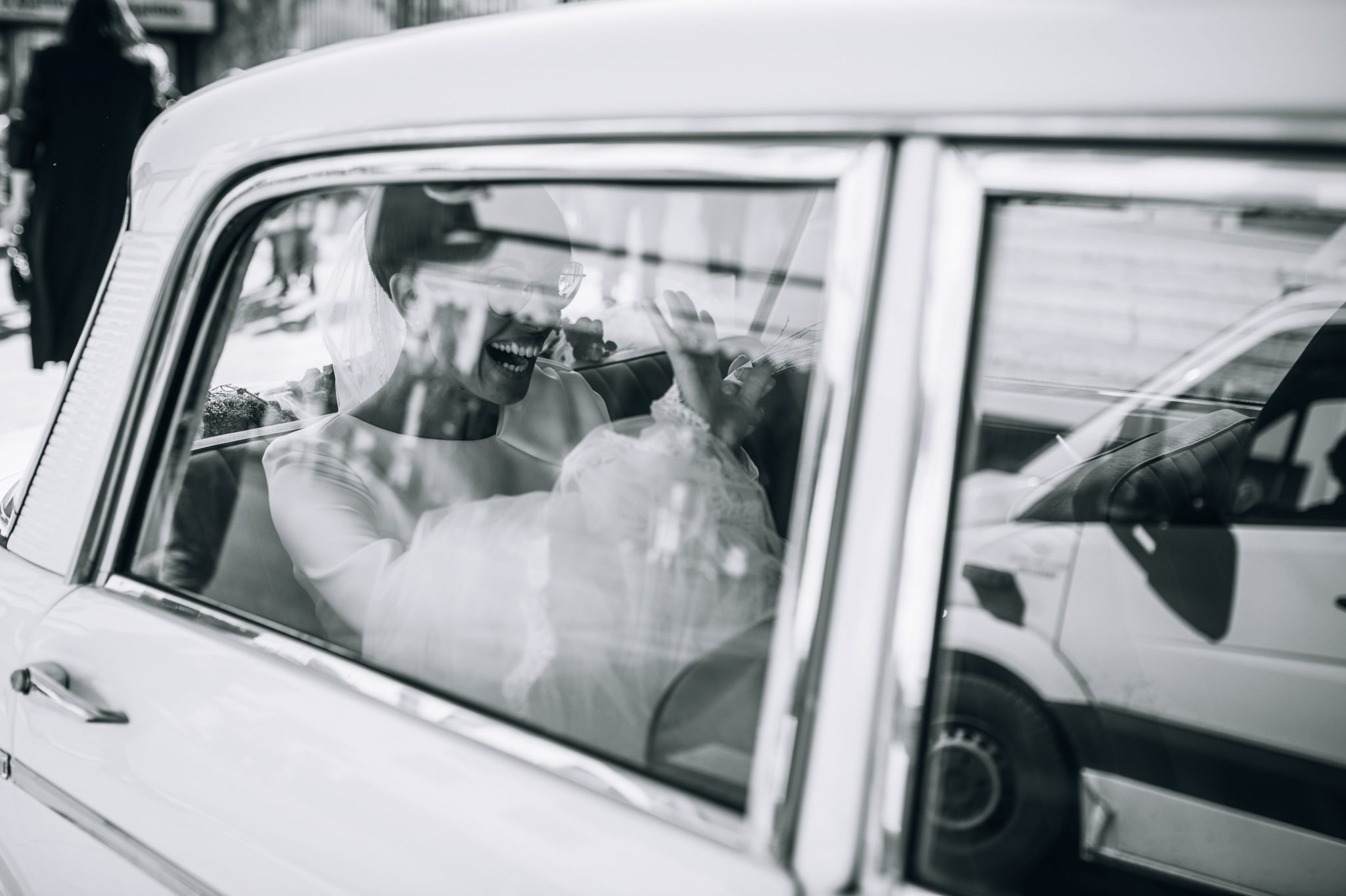 la sposa all'interno della macchina saluta sorridendo