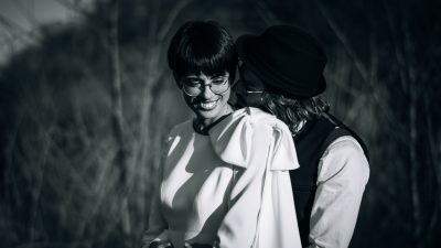 la sposa ride mentre lo sposo le sussurra delle parole all'orecchio