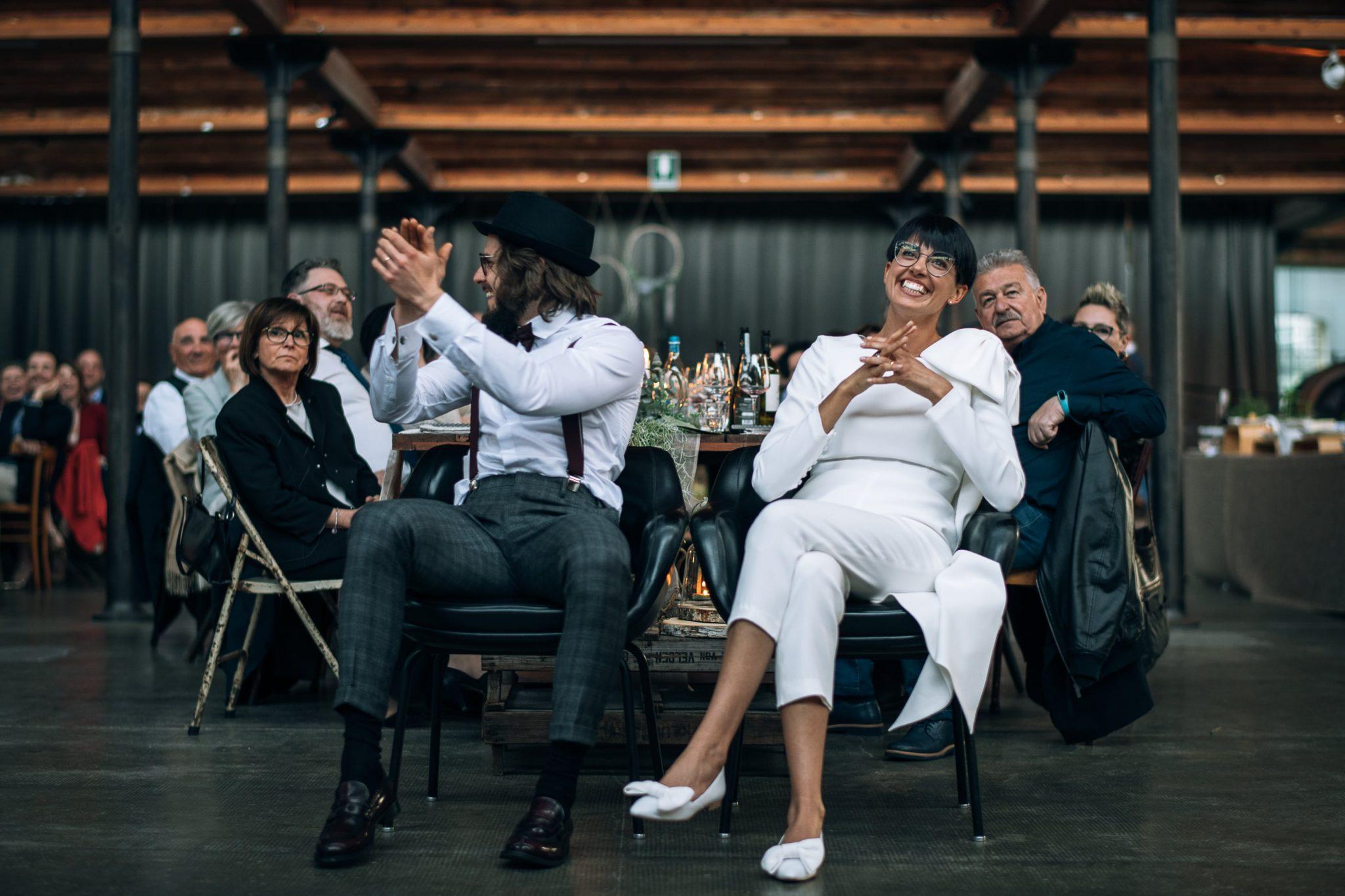 gli sposi ridono e applaudono mentre guardano i filmati con gli invitati