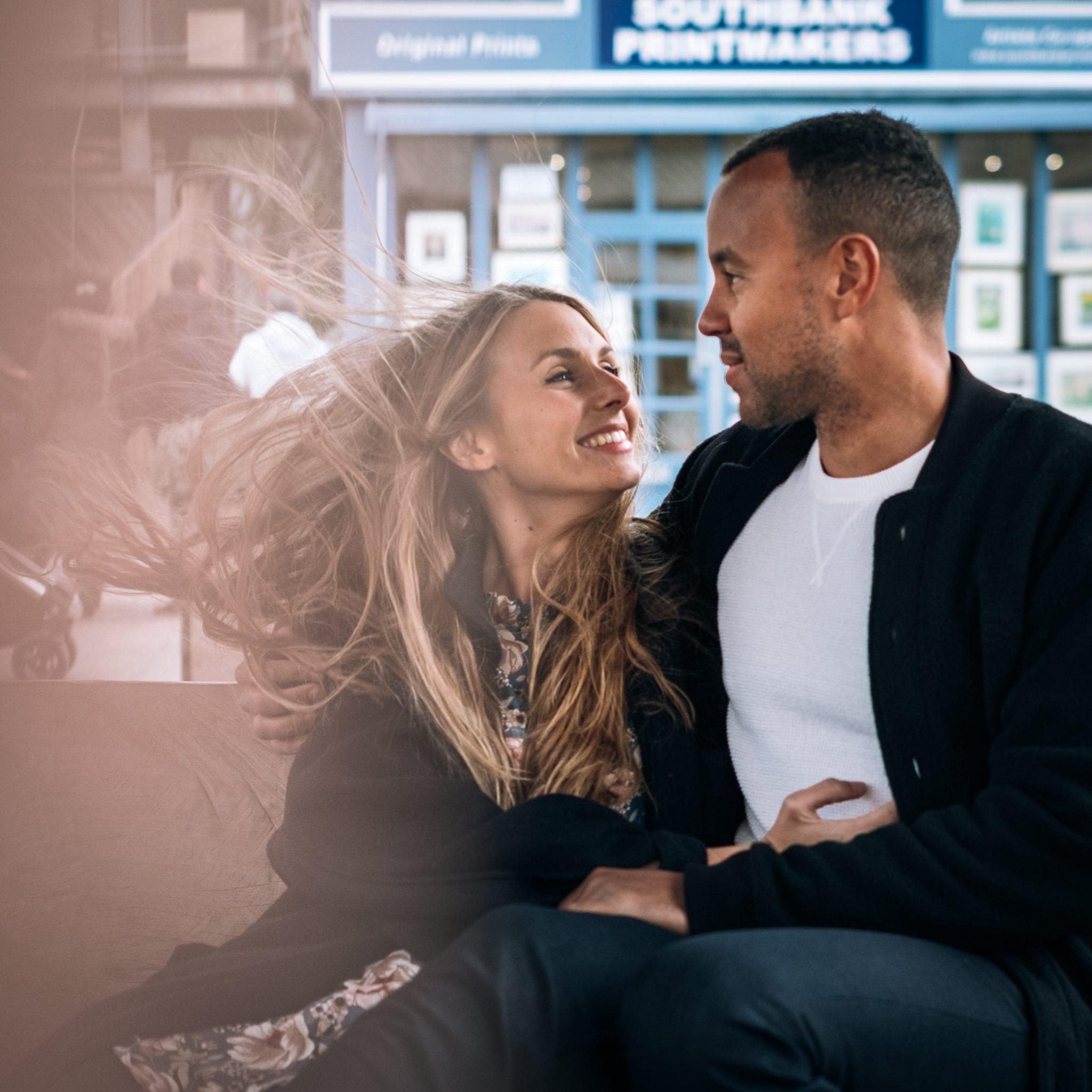 una coppia di fidanzati si scambiano dolci sguardi seduti su una panchina