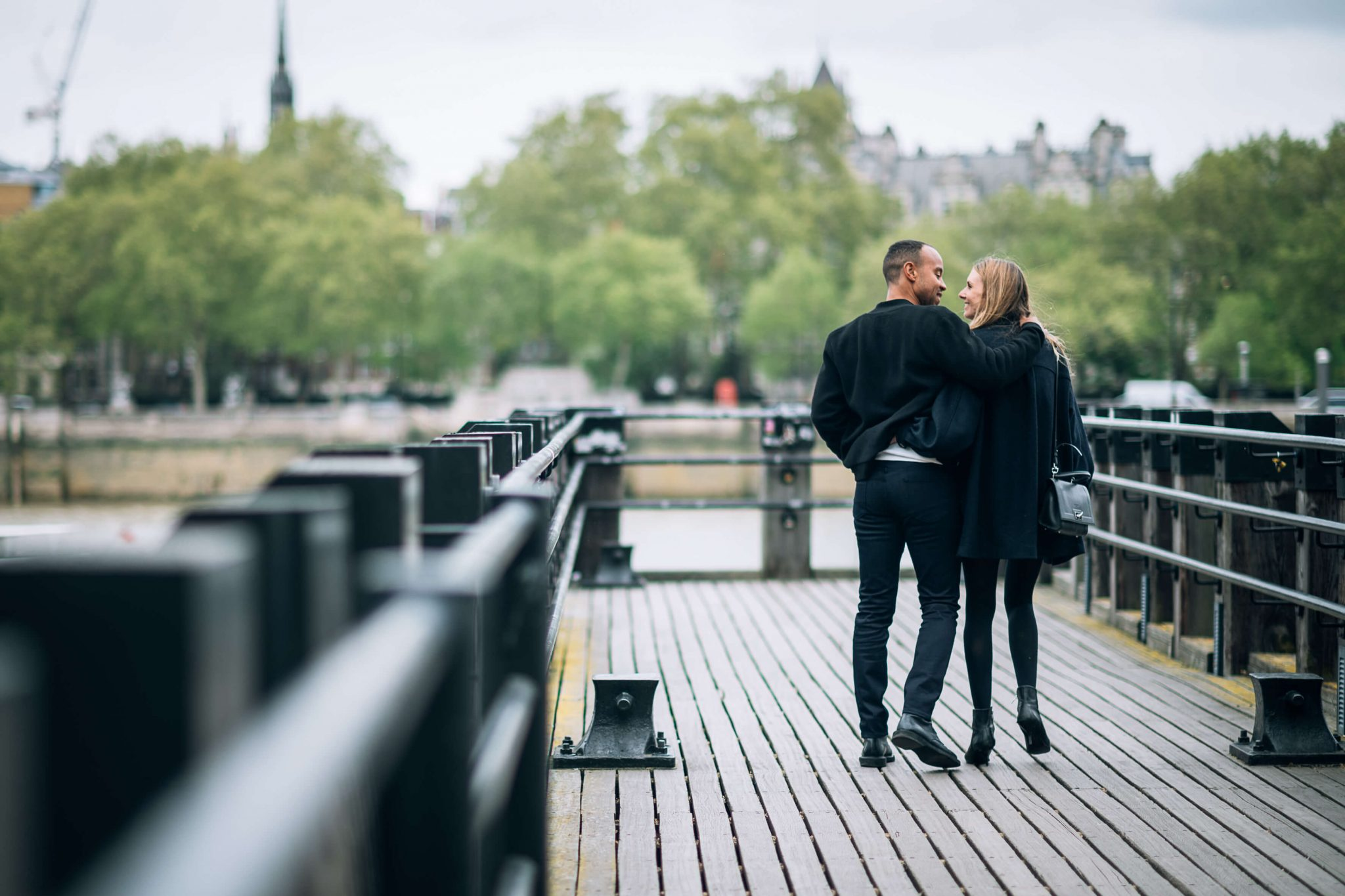 due fidanzati passeggiano sopra un ponte della città di Londra