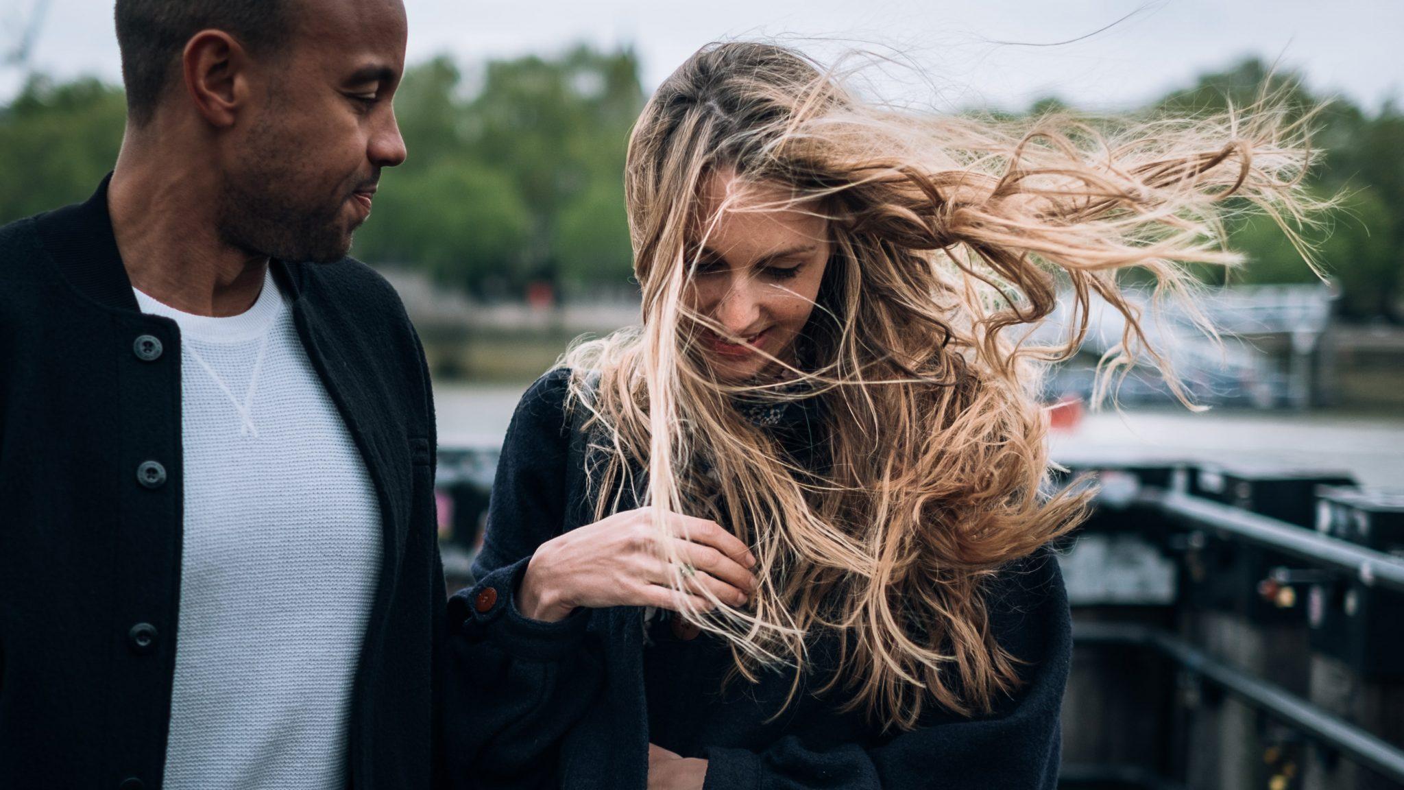 il fidanzato guarda la fidanzata mentre ha i capelli scompigliati dal vento