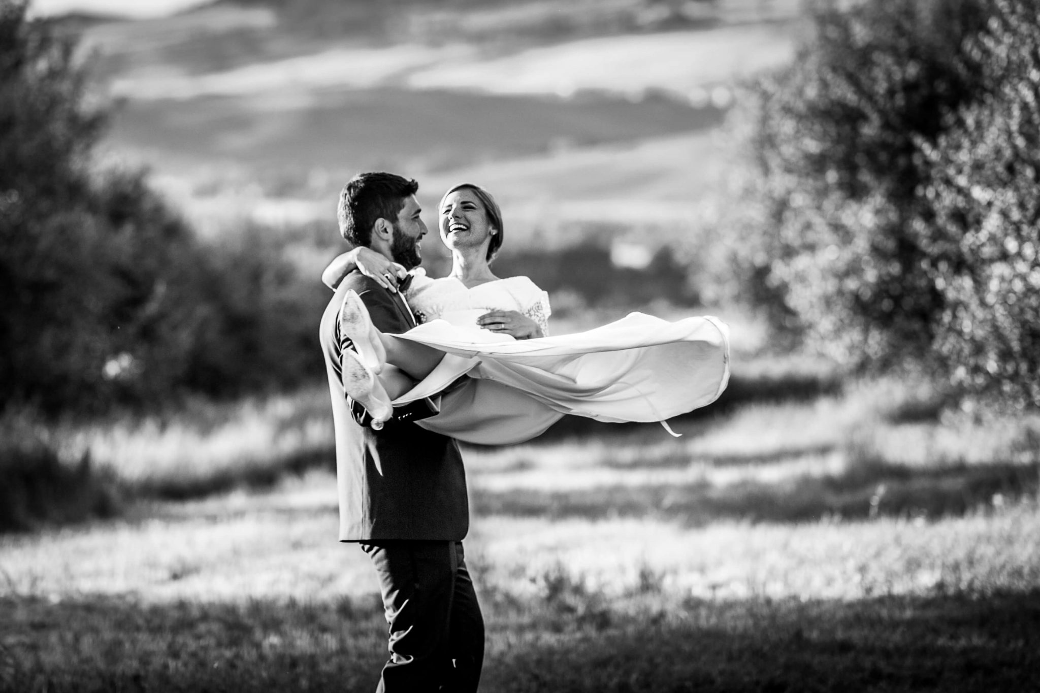 lo sposo prende in braccio la sposa divertiti in mezzo agli ulivi
