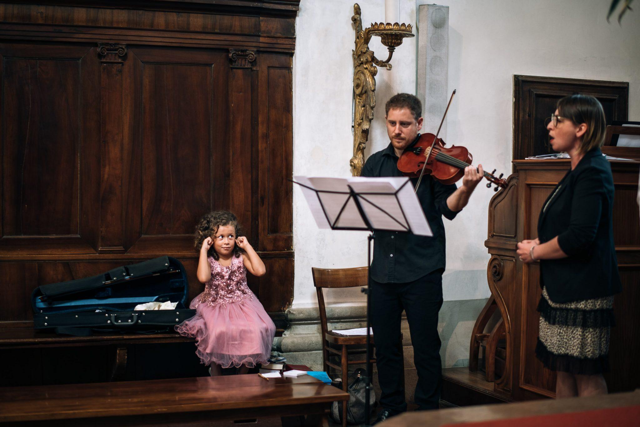 la bambina si tappa le orecchie mentre il violinista suona il violino durante la cerimonia