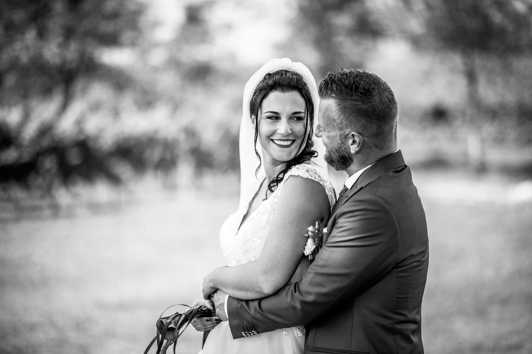 la sposa sorride allo sposo mentre si abbracciano