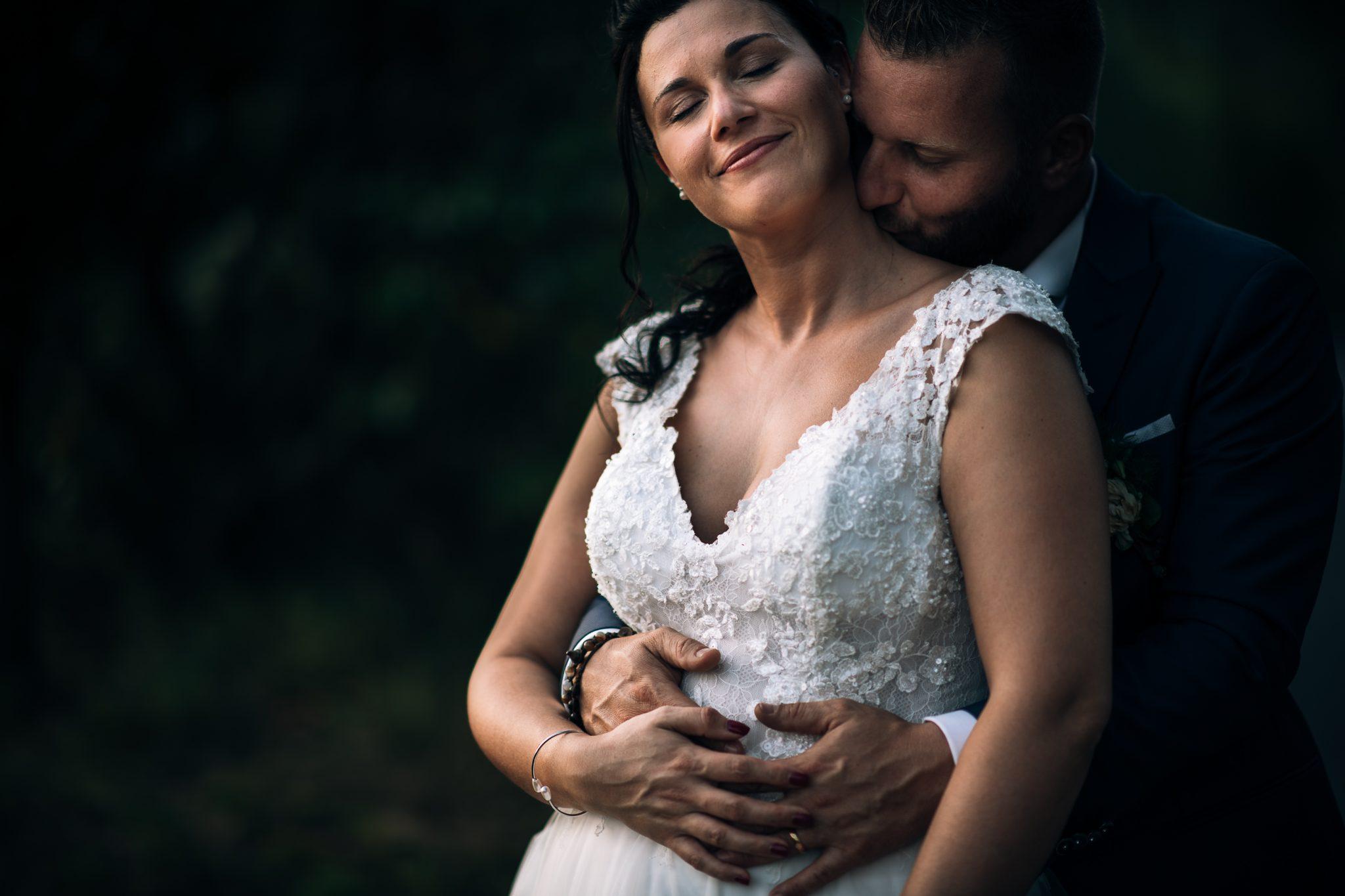lo sposo abbraccia la sposa mentre le da un bacio sul collo al matrimonio