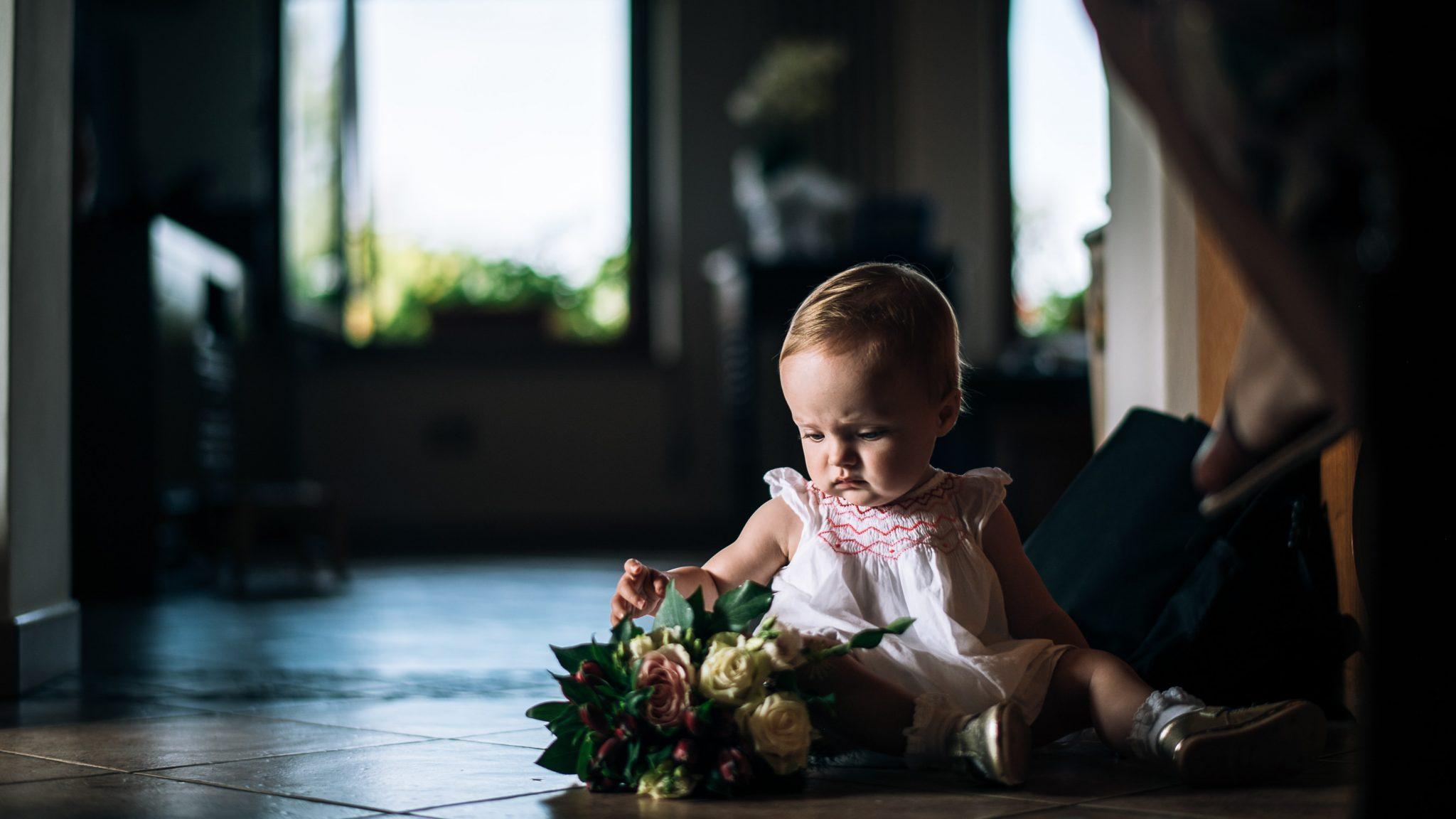 una bambina piccola seduta sul pavimento gioca con il bouquet della sposa