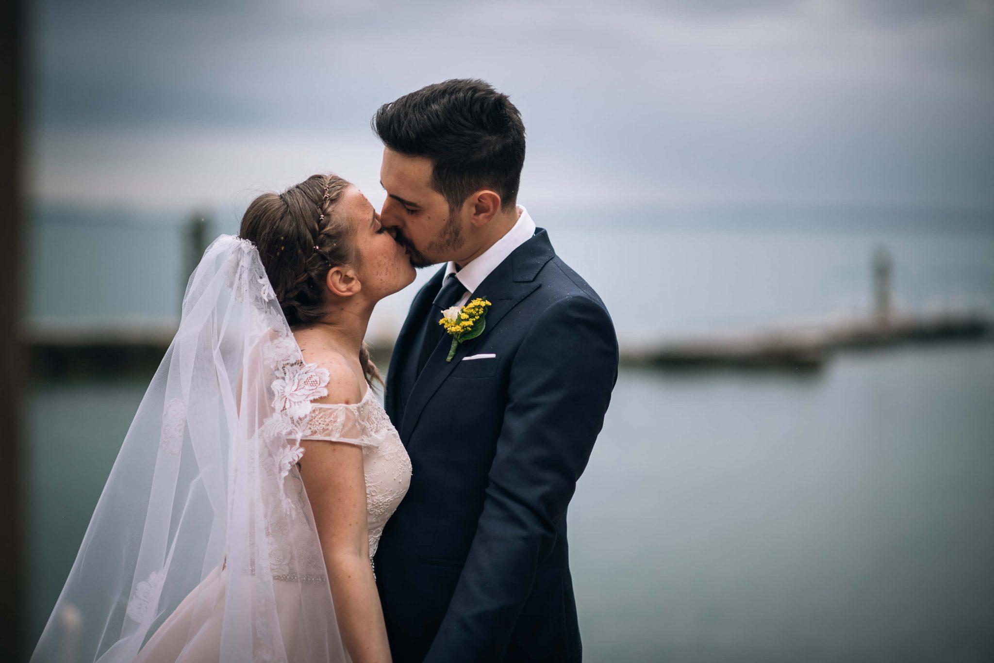 gli sposi si scambiano un bacio con alle spalle il lago