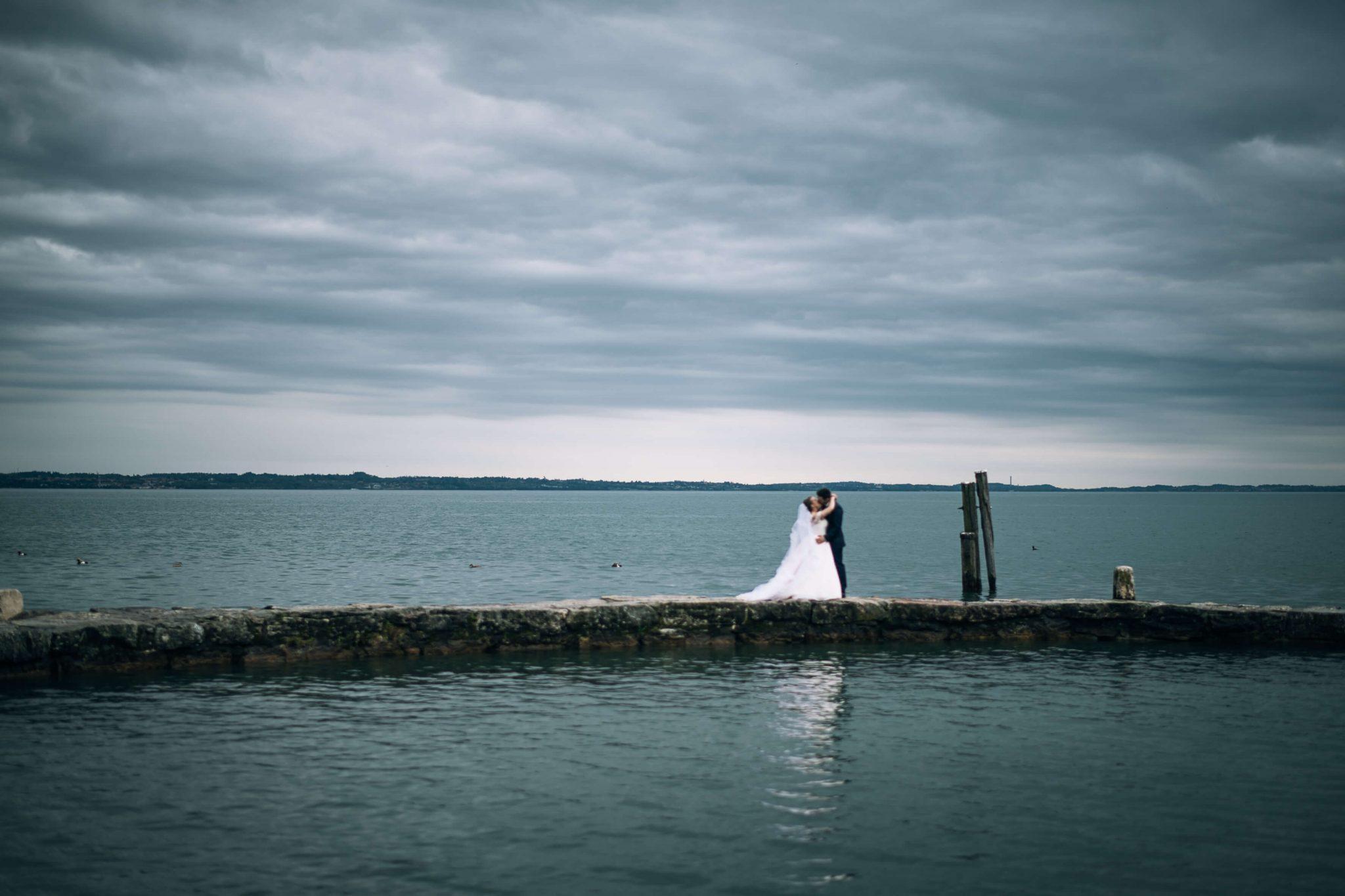 gli sposi si scambiano un bacio sulla passerella sopra al lago