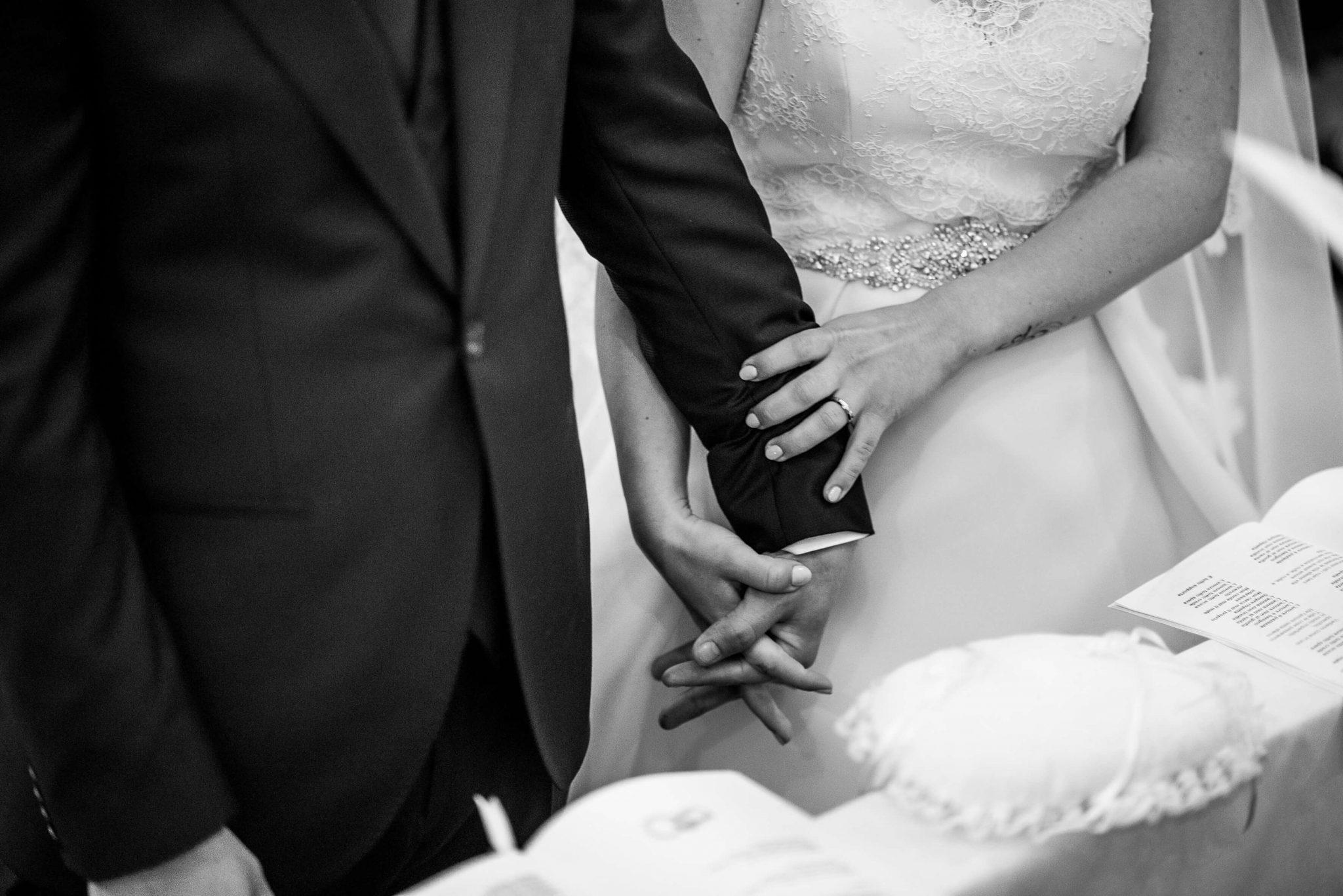 le mani intrecciate degli sposi con le fedi