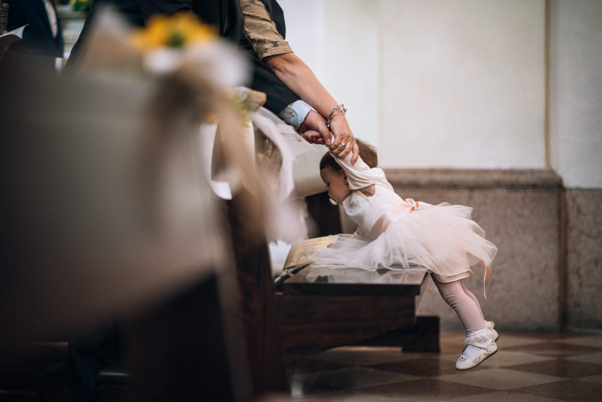 una bambina sulla panca della chiesa durante la celebrazione del matrimonio