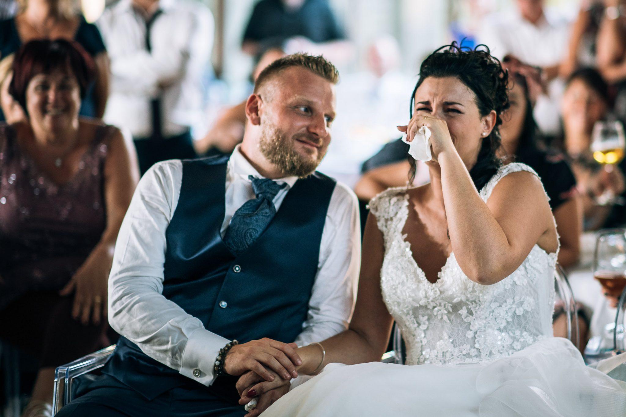 la sposa si commuove insieme allo sposo mentre guardano i video