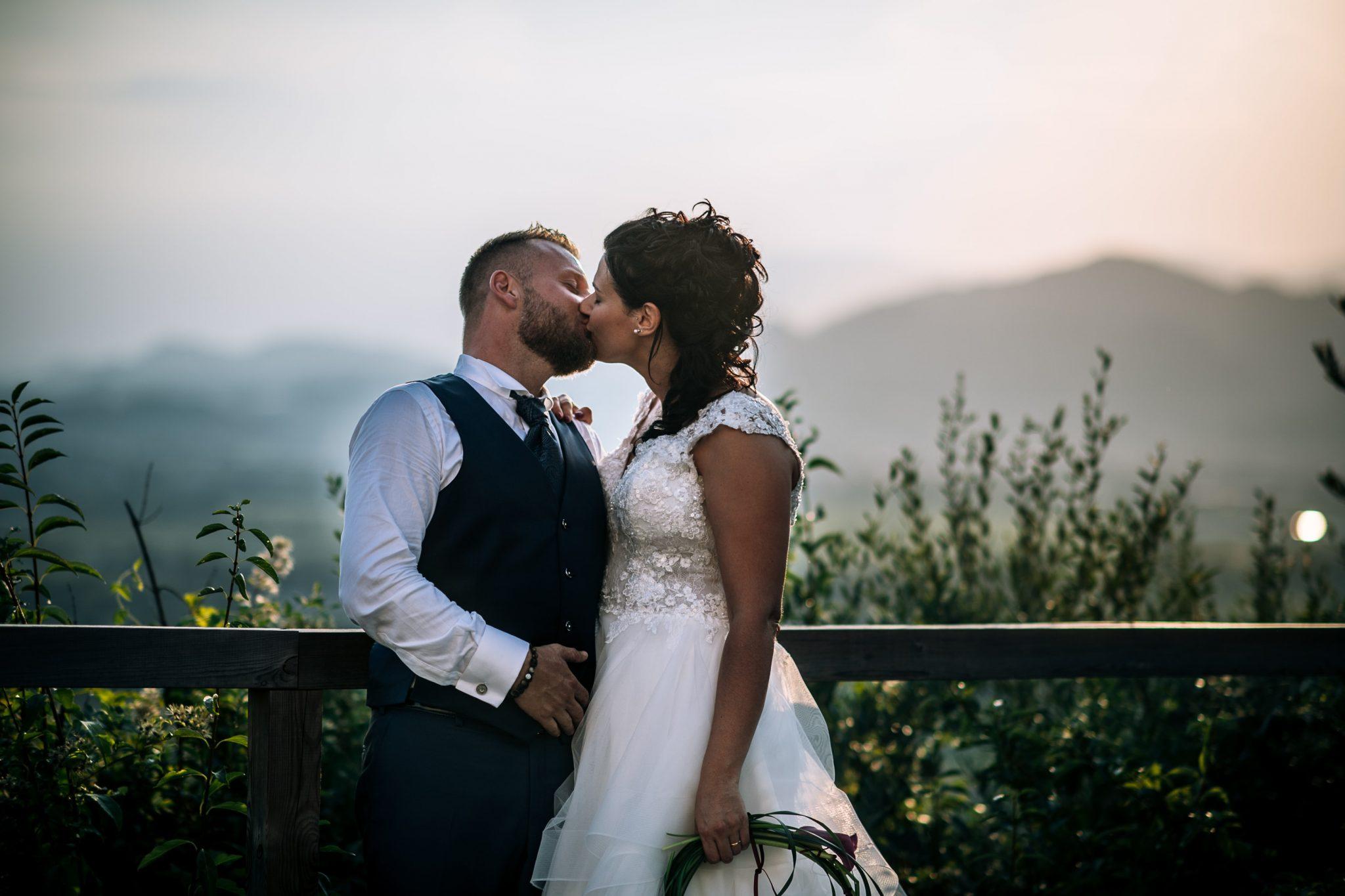 gli sposi mentre si baciano durante il tramonto