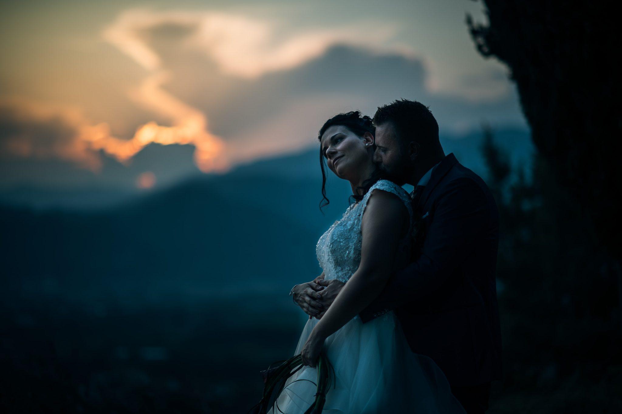 gli sposi si abbracciano e baciano durante il tramonto