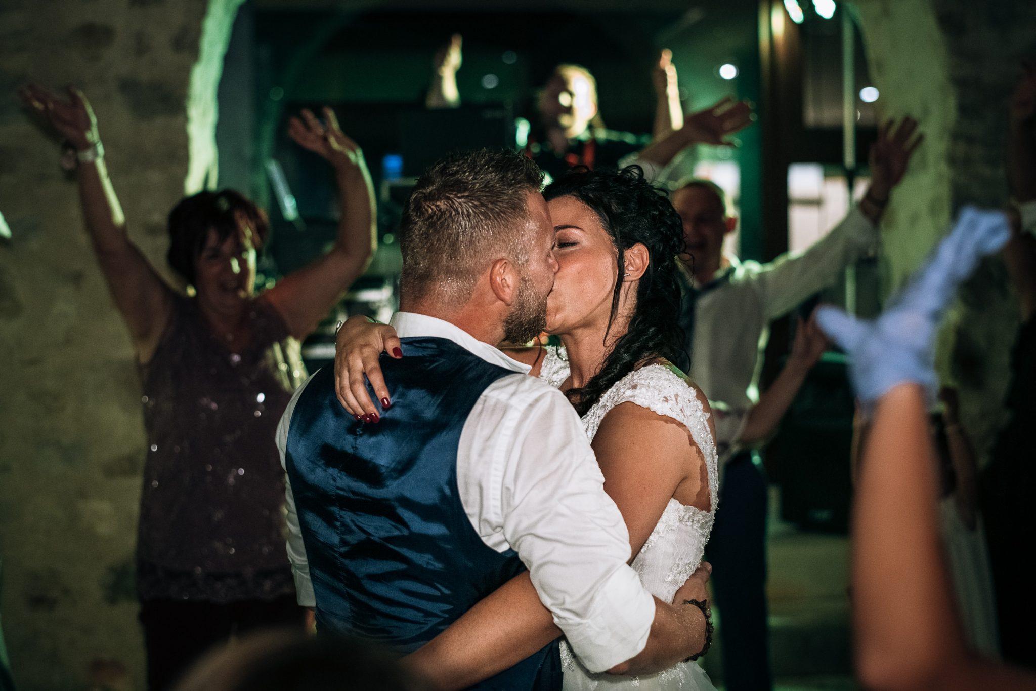 gli sposi mentre si baciano in mezzo agli invitati al palo del ricevimento