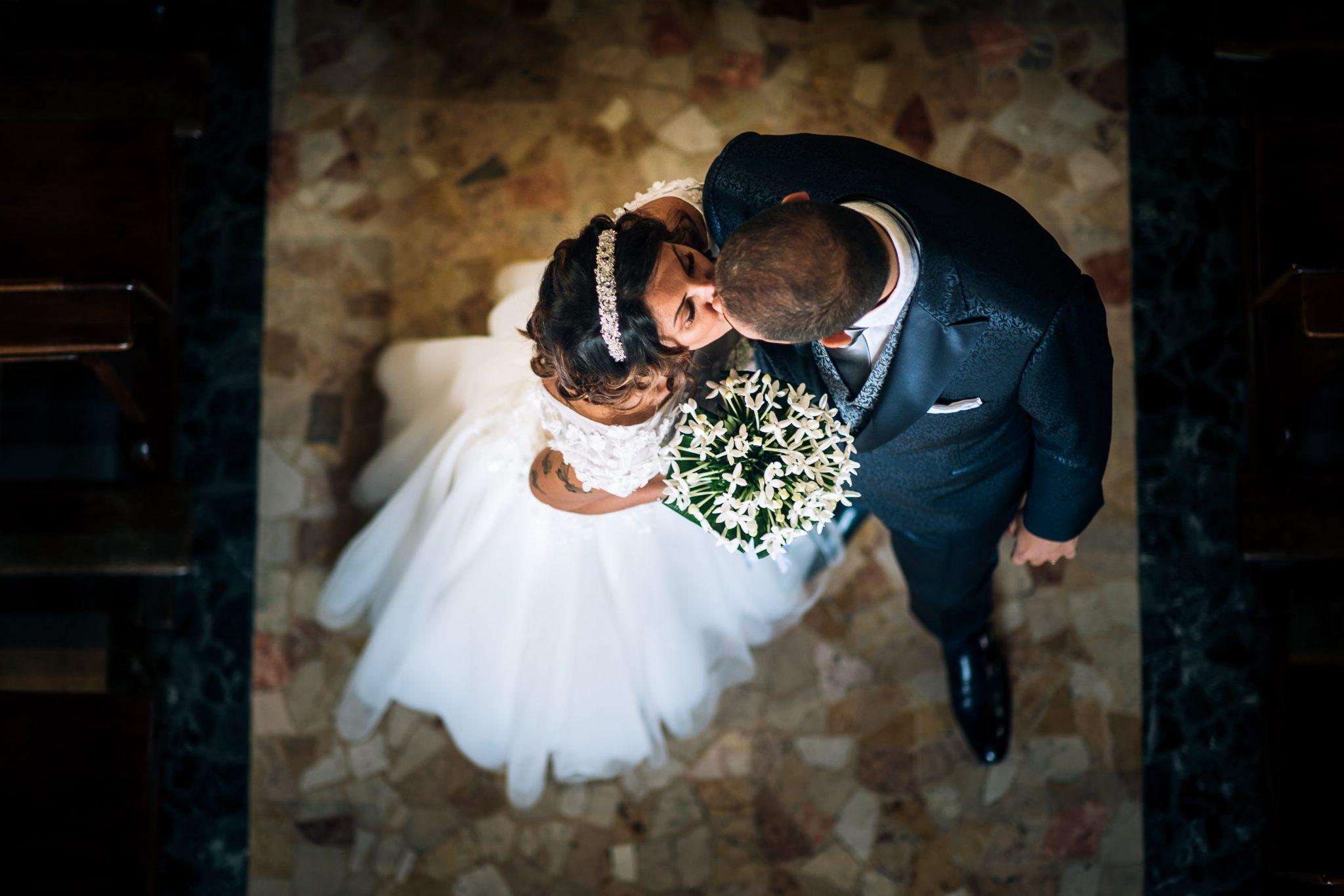gli sposi mentre si baciano in chiesa