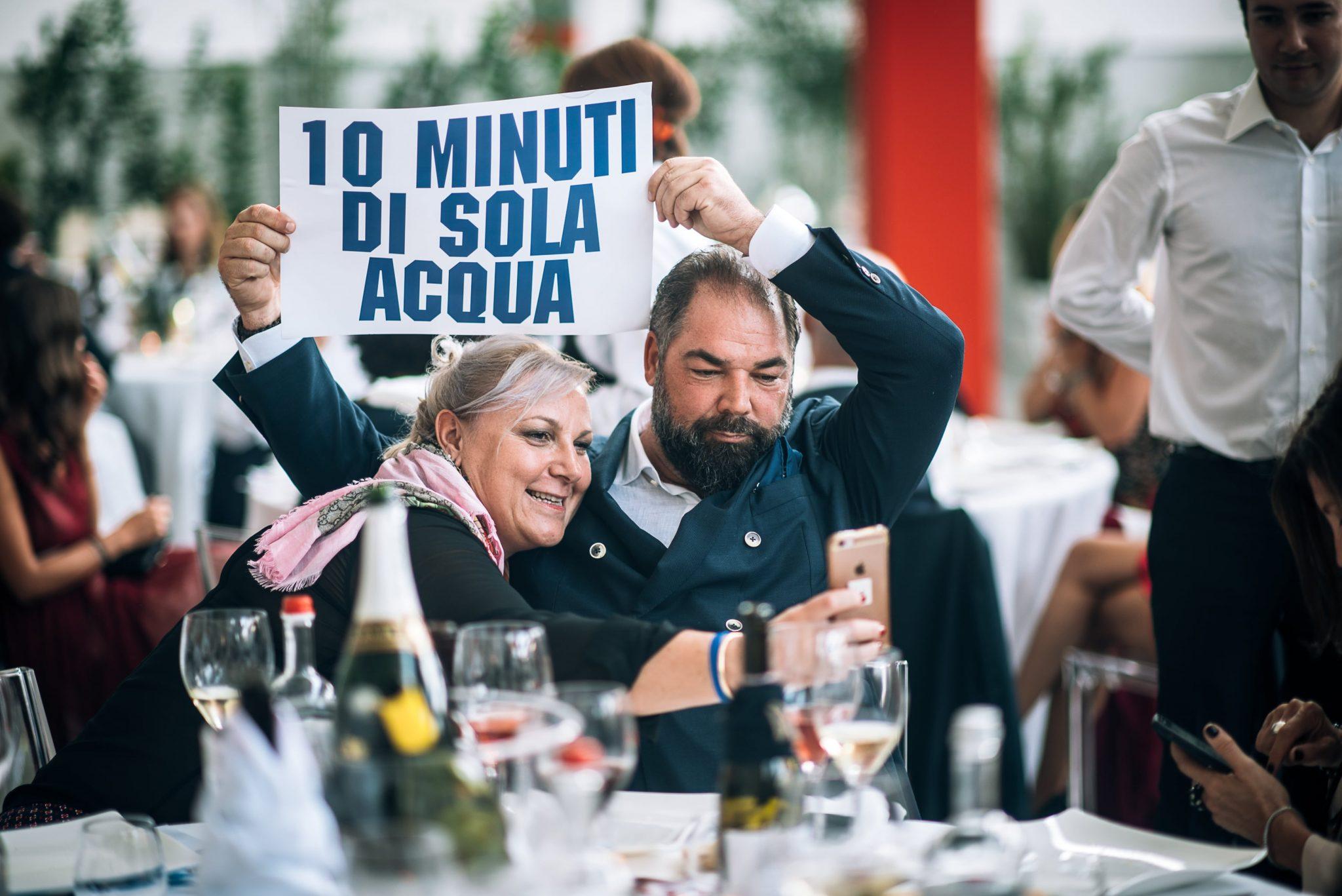 una coppia di invitati al matrimonio si scattano un selfie con un cartello durante il ricevimento