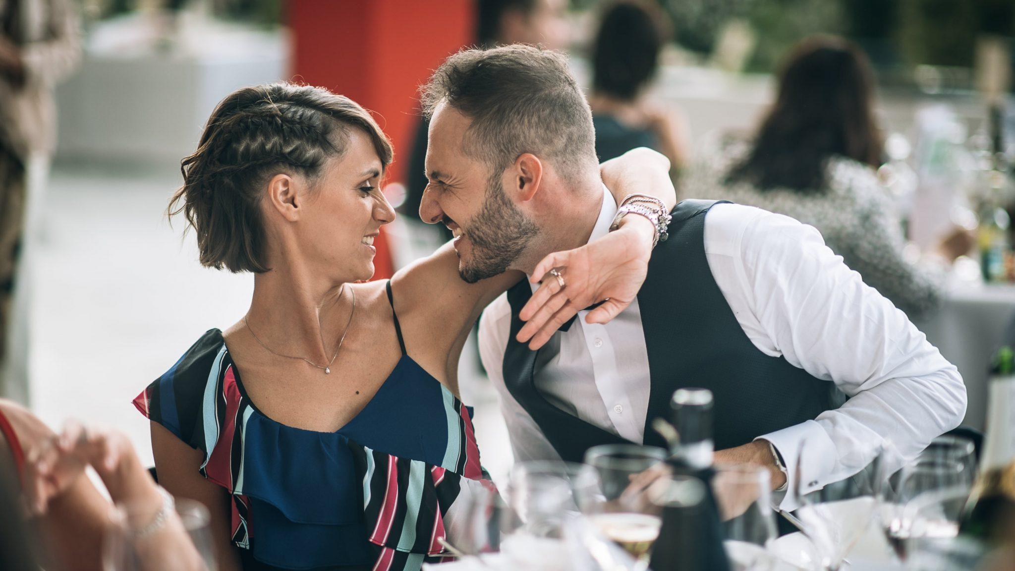 una coppia di amici degli sposi si abbracciano divertiti al ricevimento